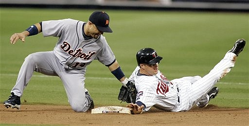 Detroit Tigers' second baseman Placido Polanco, left, is late with the tag as Minnesota Twins' Matt Tolbert, right, steals second during the second inning of a baseball game, Sunday, Sept. 20, 2009, in Minneapolis. (AP Photo/Paul Battaglia)