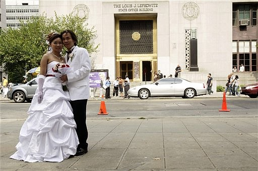 FILE - In this Sept. 9, 2009, file photo Kian Lee, right, and his bride Maya Ong, both from Queens, pose for a photo after their wedding ceremony at the Manhattan Marriage Bureau in New York. A broad array of U.S. census data, for release on Tuesday, Sept. 22, 2009, indicates that the recession is profoundly disrupting American life. Unlike the Ongs  nearly one in three Americans 15 and over, or 31.2 percent, reported they had never been married, the highest level in a decade. The share had previously hovered for years around 27 percent, before beginning to climb during the housing downturn in 2006. The never-married included three-quarters of men in their 20s and two-thirds of women in that age range. (AP Photo/Mary Altaffer, Fille)