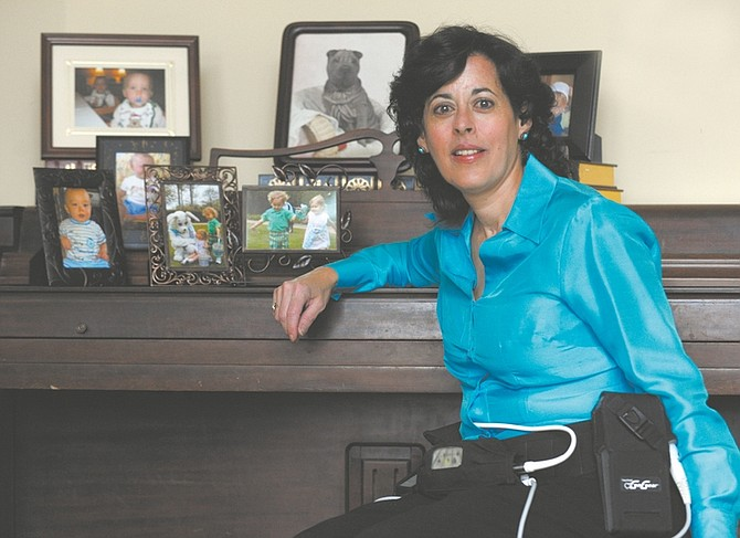 In this  Nov. 13, 2009 photo, Leonor Ortiz Childers, 46, who developed heart failure suddenly when she had to be treated for breast cancer while pregnant with her second set of twins, poses at her home in Durham, N.C. The HeartMate II heart pump, which is seen around her waist, has kept Leonor alive for a year without the need of a heart transplant. (AP Photo/Sara D. Davis)