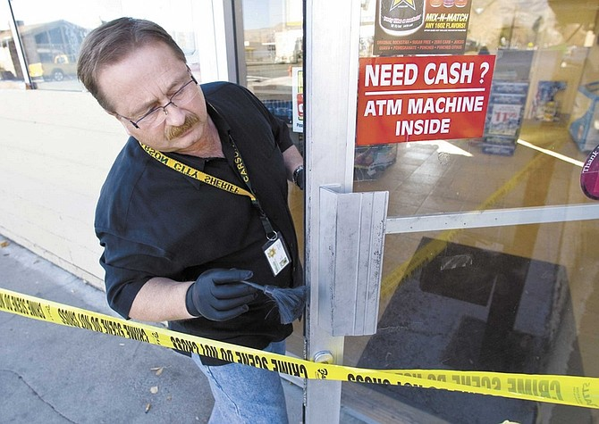 Cathleen Allison/Nevada AppealCarson City Senior Forensic Specialist Dean Higman dusts for fingerprints at the Frontier Market on Wednesday morning after the shop was robbed by three men.