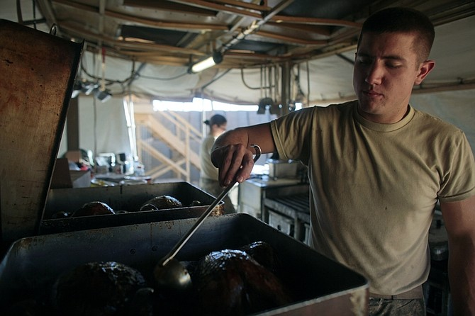 Spc. Seth Breesawitz of Springfield, Mo. head cook for the Able Troop 3-71 Cavalry Squadron, uses a ladle to baste his turkeys as he prepares Thanksgiving dinner for the troops at the Joint Combat Operations Post in the town of Baraki Barak district, Logar province, Afghanistan Thursday Nov. 26, 2009. (AP Photo/Dario Lopez-Mills)