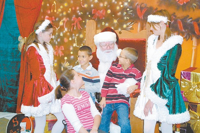 Sandi Hoover/Nevada AppealSanta Claus (Al Terpening) listens to Christmas wish lists from Tony Gurrieri, 5, left, and his brother Tyler Gurrieri, 7, while their big sister Brittany Baily, 12, looks on Saturday in the Carson Mall. Santa's helpers are Kacey Coleman, 12, left, and Bailey Furry, 13. Santa will be in the mall taking requests through Christmas on Thursdays and Fridays from 3-6 p.m., and on Saturdays and Sundays from 12-6 p.m. Christmas week Santa will be on hand Monday through Thursday from 12-6 p.m. Kids and well-behaved pets are welcome.