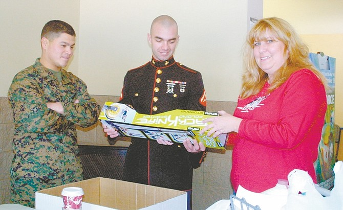 Sandi Hoover/Nevada AppealCharise Whitt of Carson City stops to chat with Marine LCPL Pierce Toomey, center, and Marine Sgt. Ruben Garcia Saturday at the north Carson City Walmart as she donates a toy for the Toys for Tots annual drive promoted by the Ron Wood Family Resource Center. They will be at the Topsy Lane Walmart in north Douglas County today between 9 a.m. and 4 p.m.