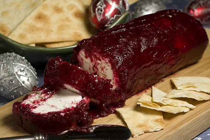 This photo taken Nov. 22, 2009 shows a cranberry goat cheese log. This dish has an intense flavor and travels well to any holiday party you may be attending.  (AP Photo/Larry Crowe)