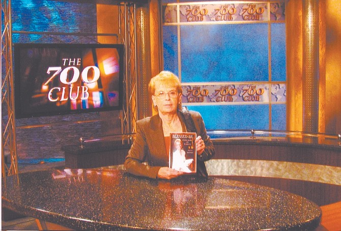 "CourtesyJulia Wells shows her book ""Blessed Be""on the set at the ""700 Club,"" which she visited after an invitation a representative of the program."