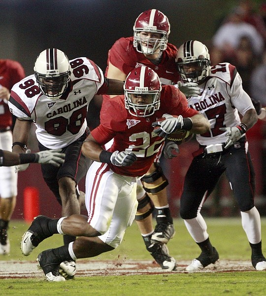 FILE - In this Oct. 17, 2009, file photo, Alabama's Mark Ingram (22) runs away from South Carolina defenders  Devin Taylor (98) and Chris Culliver (17) during the first half of an NCAA college football game at Bryant-Denny Stadium in Tuscaloosa, Ala. Ingram won the Heisman Trophy on Saturday, Dec. 12, 2009. (AP Photo/Dave Martin, File)