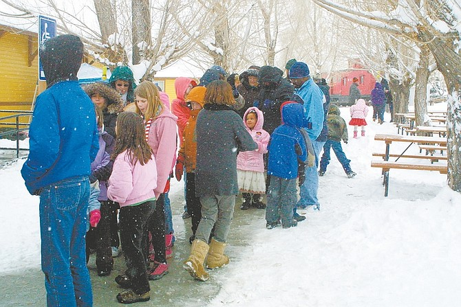 Sandi Hoover/Nevada AppealA long line of passengers curves from the depot around the sidewalk near the Nevada State Railroad Museum Saturday while waiting to board the Santa Train as snow continues to fall.