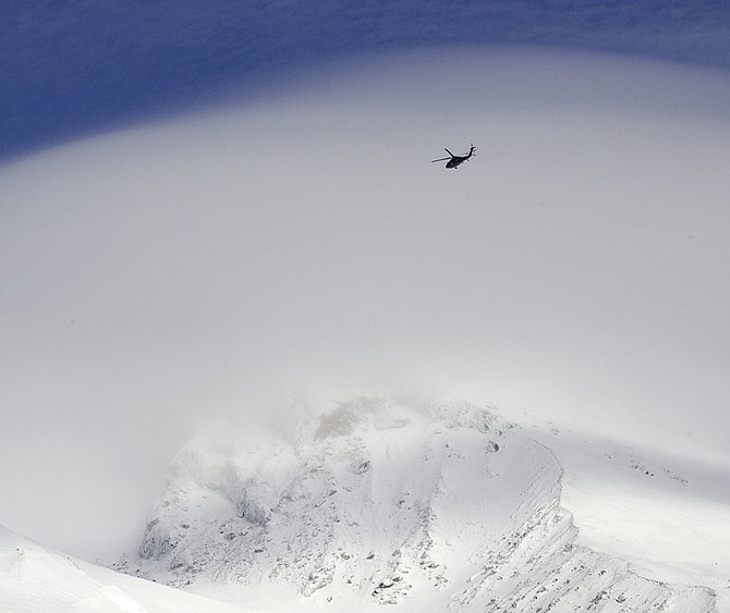 An Oregon National Guard Blackhawk helicopter flies over cloud-shrouded Mount Hood as the search for two missing climbers continues as seen from Timberline Lodge in Government Camp, Ore., Monday, Dec. 14, 2009. Weather conditions improved early in the day  allowing searchers a window of opportunity to search for Anthony Vietti, 24, of Longview, Wash., and Katie Nolan, 29, of Portland, before a large winter storm blows in later in the day. (AP Photo/Don Ryan)