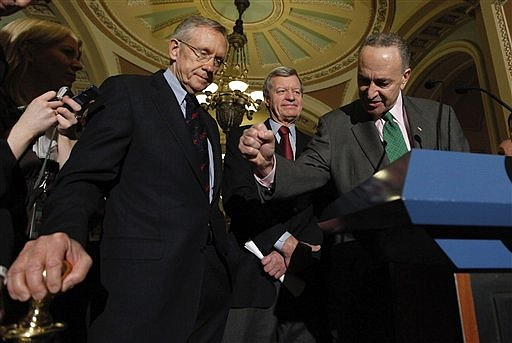 Senate Majority Leader Harry Reid of Nev., left,  listens as Sen. Charles Schumer, D-N.Y., right, drives home a point while answering questions on Capitol Hill in Washington, Thursday, Dec. 24, 2009, after the Senate passed the health care reform bill. Senate Finance Committee Chairman Sen. Max Baucus, D-Mont. is at center.  (AP Photo/Manuel Balce Ceneta)