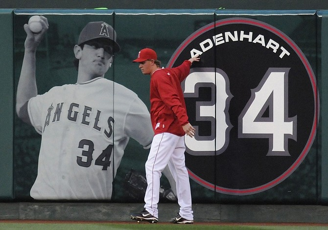 ** FOR USE AS DESIRED, YEAR END PHOTOS ** FILE - Los Angeles Angels  starting pitcher Jered Weaver pays his respect at a center field banner of Los Angeles Angels rookie pitcher Nick Adenhart who was killed early Thursday in an auto accident in Fullerton, Calif., before their baseball game with the Boston Red Sox in Anaheim, Calif., in this April 10, 2009 file photo. (AP Photo/Chris Carlson, File)