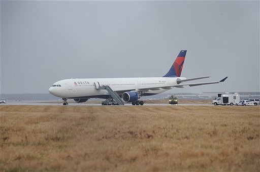 ** CORRECTS TO REMOVE REFERENCE TO FIRECRACKERS ** This picture provided by J.P. Karas shows Northwest Airlines Flight 253 on the runway after arriving at Detroit Metropolitan Airport from Amsterdam on Friday, Dec. 25, 2009. Officials say a passenger aboard the plane was trying to ignite an explosive device Friday, causing a commotion and minor injuries. (AP Photo/J.P. Karas)