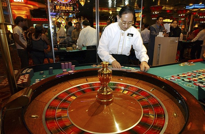 FILE - In this July 4, 2006 file photograph, Tommy Yu, a roulette dealer at Resorts Atlantic City casino, counts chips during play in Atlantic City, N.J. According to a new poll released Thursday, March 11, 2010, a majority of Americans oppose changing the law to allow bets to be placed over the Internet, as well as to allow legal betting in professional or college sports teams. The Fairleigh Dickinson University PublicMind poll also found people have positive opinions of Las Vegas, Atlantic City, and most other gambling resorts, with only Detroit receiving a negative rating. (AP Photo/Mary Godleski, File)