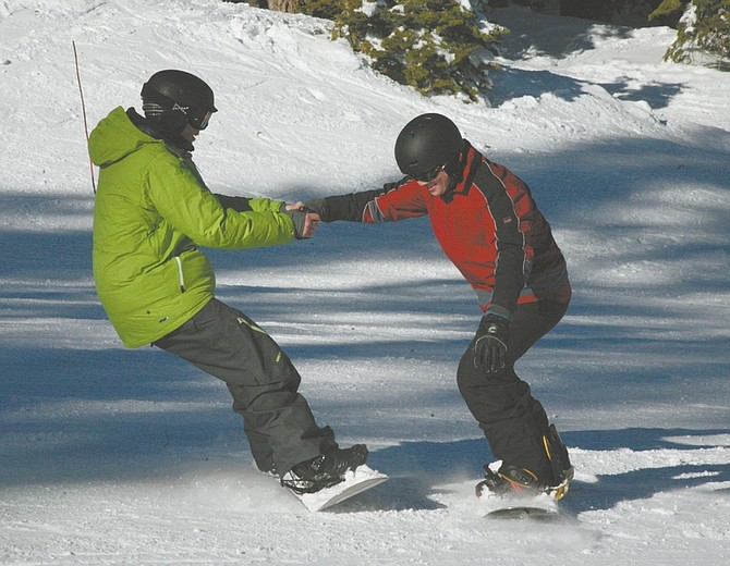 Matthew Renda/Nevada Appeal News ServiceBurton Snowboard Academy Manager Chris Hargrave holds onto Sierra Sun reporter Jason Shueh, as Shueh attempts to learn the fundamentals of making turns on the snowboard.