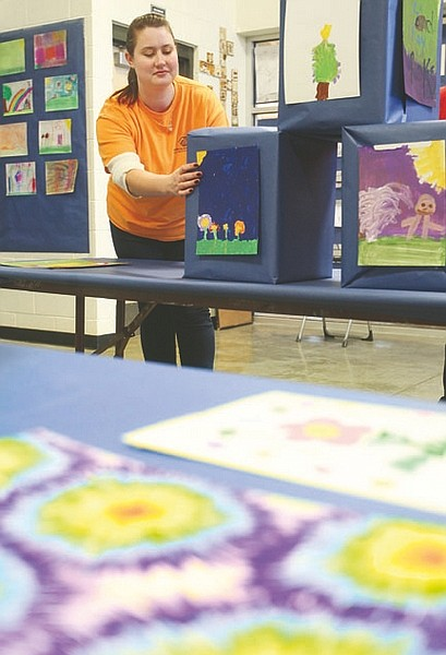 Jim Grant/Nevada AppealRohne Flaig, education coordinator at the Boys & Girls Club tapes art work to a display box on Tuesday for the club's fine art show.