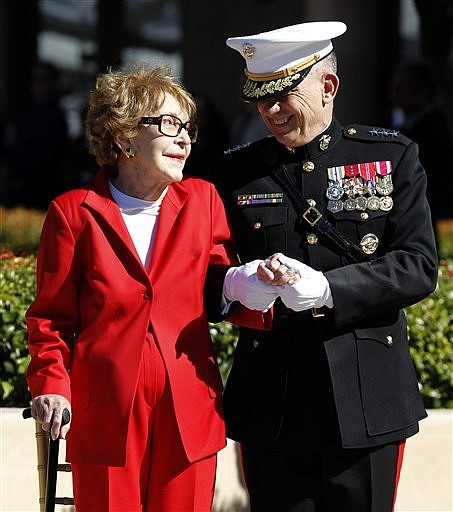 Former first lady Nancy Reagan is helped by Marine Lt. Gen. George J. Flynn as she arrives for a wreath laying ceremony at the memorial of her husband former U.S. President Ronald Reagan during the centennial birthday celebration at the Ronald Reagan Presidential Library in Simi Valley, Calif., Sunday, Feb. 6, 2011. (AP Photo/Chris Carlson)