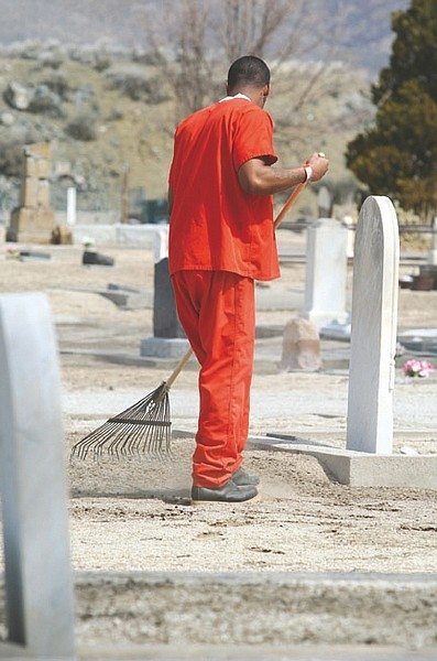 Jim Grant/Nevada AppealParticipating in a work crew, an inmate from the Carson City jail cleans up yard debris Tuesday that could foster weed growth around graves at the Lone Mountain Cemetery.