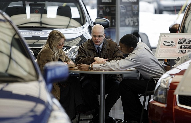 In this March 14, 2011 photo, Kelley and Ed Postal, of Pinckney, Mich., from left, work with salesman Darnell Forte at a Nissan dealership in Ann Arbor, Mich. Consumer spending rises at fastest pace since October, led by purchases of autos and gasoline.(AP Photo/Paul Sancya)