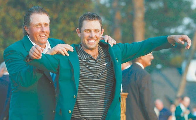 Former champion Phil Mickelson, back, helps Charl Schwartzel of South Africa with his green Masters jacket after winning the Masters golf tournament Sunday, April 10, 2011, in Augusta, Ga. (AP Photo/Matt Slocum)