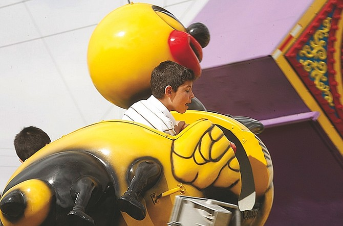 Shannon LItz/Nevada AppealEight-year-old Ivan Iza peeks over the side of the Buzzin' Bee ride while riding with his brother, Ari, 5, at the RSVP Carnival.