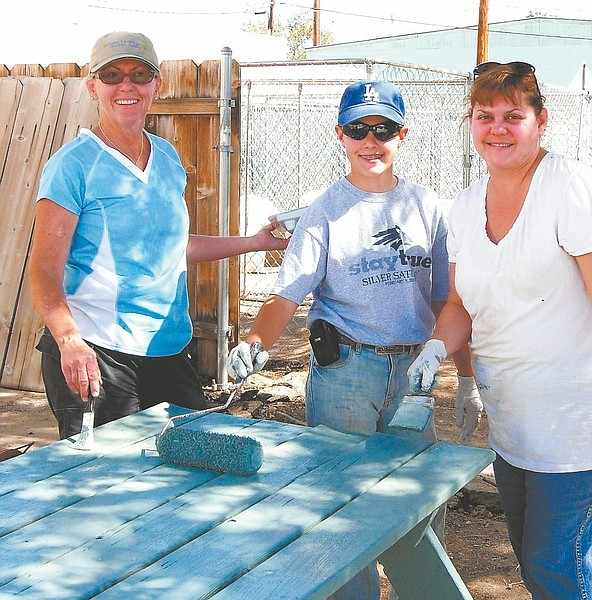 Published Caption: Carson City Leadership Class 2010 class project coordinator Margie Quirk, left, assists Noah Jennings and his mother, Stacy Woodbury, with the painting of one of the tables at the animal shelter.