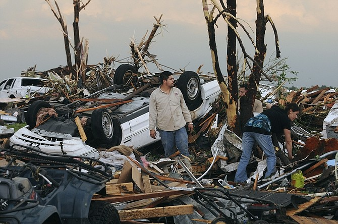 Residents begin digging through the rubble of their home after it was destroyed by a tornado that hit Joplin, Mo. on Sunday evening, May 22, 2011. The tornado tore a path a mile wide and four miles long destroying homes and businesses. (AP Photo/Mike Gullett)