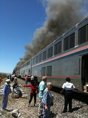 In this photo provided by Ron Almgren.  passengers and Amtrak train staff are seen at the site of a collision between an Amtrak westbound train and a truck on  U.S. 95 about 4 miles south of Interstate 80 on Friday, June 24, 2011, 70 miles east of Reno, Nev. The truck driver and one person on the train were killed said Nevada Highway Patrol Trooper Dan Lopez. An unknown number of other people on the train were injured and were being taken by ambulances to the hospital.  (AP Photo/Ron Almgren)