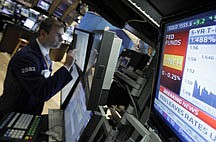 A television monitor shows the interest rate decision of the Federal Reserve as specialist Philip Finale works on the floor of the New York Stock Exchange Wednesday, June 22, 2011. The Federal Reserve acknowledged that the economy is growing more slowly than it expected. But it plans to complete its $600 billion Treasury bond buying program by the end of the month. (AP Photo/Richard Drew)