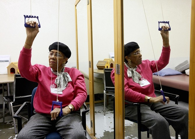 This March 8, 2011 photo shows Genevive Cotton working out at the Adult Day Health Care center in Los Angeles.  Deep cuts in the state's Medicare spending may gut adult day care programs that give seniors a safe place to spend their days while their relatives are at work.    (AP Photo/Nick Ut)