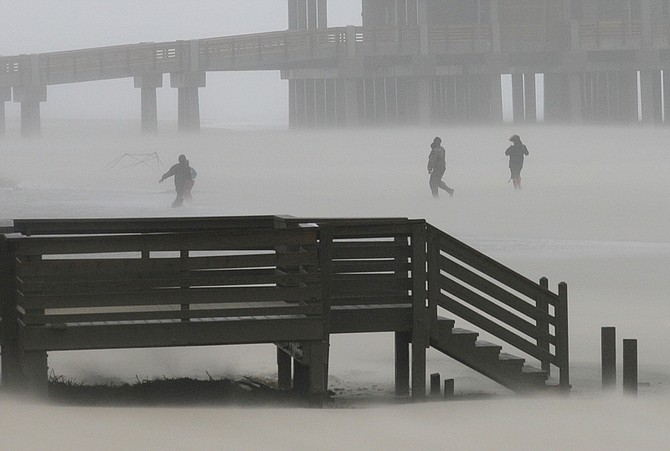 People walk through the blowing rain and sand as the effects of Hurricane Irene are felt in Nags Head, N.C., Saturday, Aug. 27, 2011. (AP Photo/Gerry Broome)