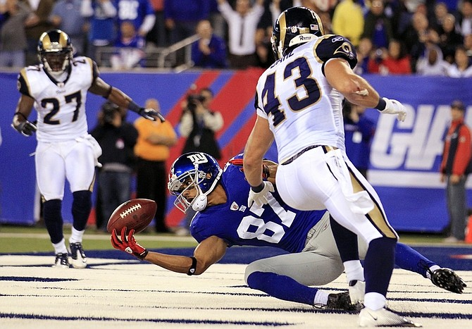 New York Giants wide receiver Domenik Hixon (87) catches a pass for a touchdown during the second quarter of an NFL football game against the St. Louis Rams on Monday, Sept. 19, 2011, in East Rutherford, N.J. Defending are Rams' Craig Dahl, right, and Quintin Mikell. (AP Photo/Julio Cortez)