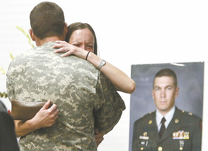 Shannon LitzStacia Greene, Master Sgt. Christian Riege's fiance, hugs a soldier before the remembrance ceremony to honor Riege, Maj. Heath Kelly and Sgt. 1st Class Miranda McElhiney on Sunday. The three were killed Tuesday in a mass shooting inside the Carson City IHOP.