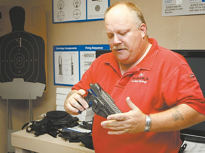 Shannon Litz/Nevada AppealJames Campbell of America West Guns talk about the different holsters available on Thursday in his Carson City shop.