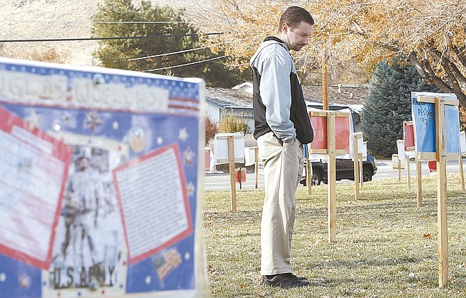 Photos by Shannon Litz/Nevada AppealCarson Middle School social studies teacher and Army veteran Jim Hannah looks at the display on the lawn of of the school Wednesday. Eighth-graders there interviewed veterans then posted their biographies on the placards in front of the school. Community members are invited to view the display through Sunday.
