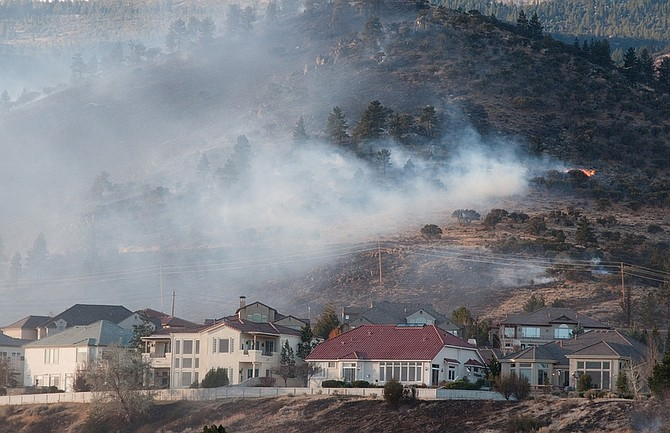 The 400-acre Caughlin Fire burns near homes  in Reno, Nev. on Friday, Nov. 18, 2011. High winds are making it difficult to contain the fire. Officials say at least a dozen homes have been lost, several people have suffered smoke inhalation and one person suffered a cardiac arrest in the fire, which started about 12:30 a.m. in the Caughlin Ranch area and glowed orange on the hillsides through the night.  (AP Photo/Kevin Clifford)