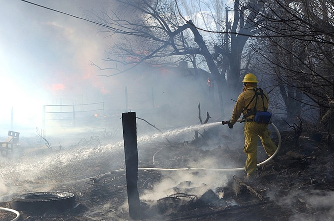 Firefighters battle a 400-acre brush fire in south Reno, Nev., on Friday, Nov. 18, 2011. The fire raged through more than 400 acres, claimed at least one life, injured several others, destroyed dozens of  homes and blanketed Reno and its suburban enclaves in a fiery curtain as violent winds sidelined firefighters and rescue helicopters.  (AP Photo/Cathleen Allison)