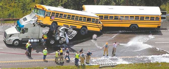 In this Aug. 5, 2010 photo, a crumpled pickup truck is seen between two St. James School District buses and a tractor-trailer on Interstate 44 near Gray Summit, Mo. Citing the wreck, in which investigators say the 19-year-old pickup driver was texting, federal transportation leaders this week pressed states to ban cell phone use by drivers. Despite the dangers, states appear unlikely to oblige. (AP Photo/St. Louis Post-Dispatch, Robert Cohen)  EDWARDSVILLE INTELLIGENCER OUT; THE ALTON TELEGRAPH OUT