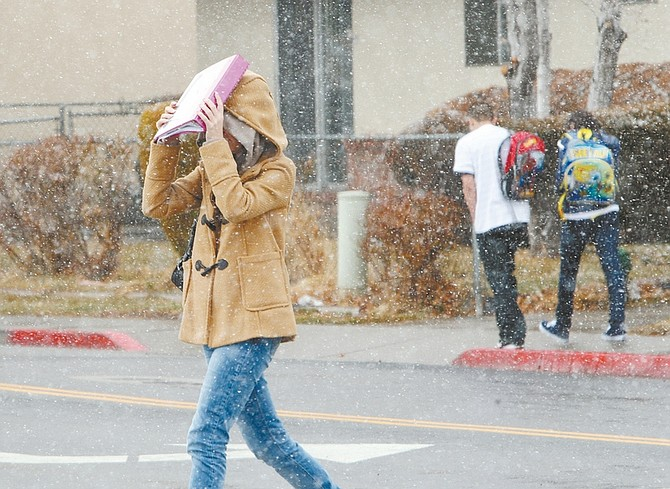 Jim Grant/Nevada AppealA Carson High School student shields her face from the snow with a notebook on Monday afternoon.