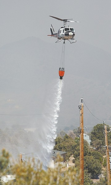 Jim Grant/Nevada AppealA helicopter makes a water drop on the Topaz Ranch Estates fire on Tuesday.