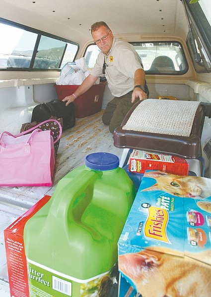 """Jim Grant / Nevada Appeal Carson City Animal Services Officer Kevin McCoy fills the back of a truck with donated items that were collected during the Sierra Veterinary Hospital's Puppy & Kitten Shower in June. The inaugural event had """"an insanely good turnout,"""" said Lori Fulmer, a technician assistant with Sierra Veterinary Hospital. Fulmer said the hospital is going to make the event yearly."""