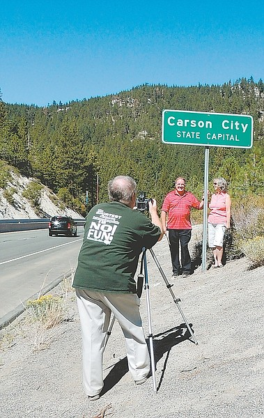 John Barrette / Nevada AppealJ. Stephen Conn and his wife, Karen, pose for a photograph taken by Oscar Voss. Conn completing his project of traveling to all U.S. counties by entering Carson City on Saturday.