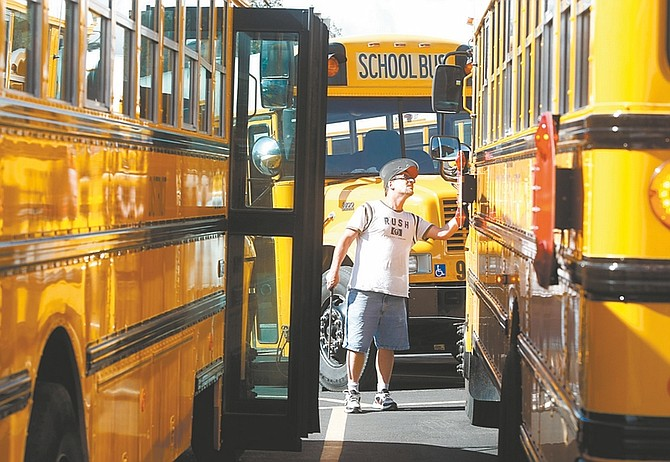 Shannon Litz / Nevada AppealScott McKee checks out his school bus before leaving the bus yard to take students home from school on Friday afternoon. The Carson City School District is facing a $5.5 million budget shortfall next year.
