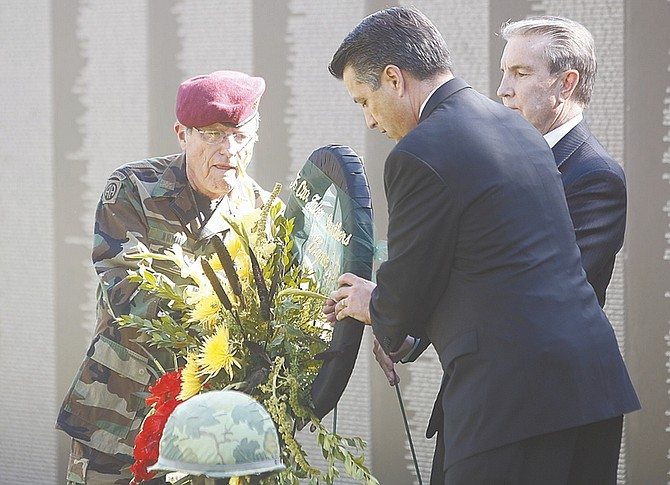Shannon Litz / Nevada AppealRick Arnold of the Vietnam Veterans of America Chapter 388, Nevada Gov. Brian Sandoval and Carson City Mayor Bob Crowell place a wreath near the Traveling Vietnam Memorial Wall on Thursday at Mills Park.