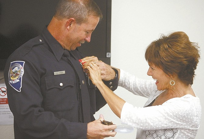 Shannon Litz / Nevada AppealTrooper Ron Larson has his new badge pinned on by his wife, Maria, on Friday afternoon. Larson was honored for being the longest serving Nevada Highway Patrol Trooper on the force.