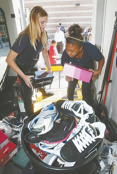 Jim Grant / Nevada AppealRaynna Jackson, 14, left, and Chyler Beck, 12, help unload 125 pairs of shoes delivered to the Boys & Girls Clubs of Western Nevada on Tuesday.