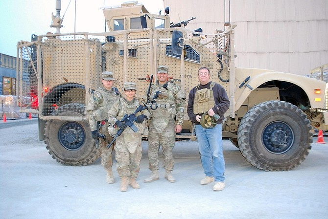 Photo by Staff Sgt. Kimberly WadsworthA convoy crew consisting of, from left, gunner Spc. David Iveson, driver Spc. Julia Rodriguez, Capt. Curtis Kolvet and Lahontan Valley News Editor Steve Ranson prepares for its departure.