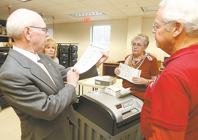 Shannon Litz / Nevada AppealCarson City Clerk-Recorder Alan Glover checks an absentee ballot Friday morning while Tanya Meed, Linda Curtis and Mike Curtis look on.