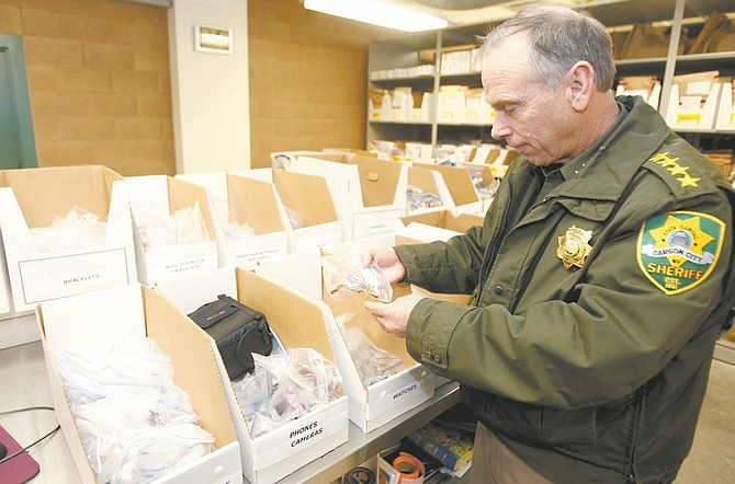 Shannon Litz / Nevada AppealCarson City Sheriff Ken Furlong looks over items collected on Friday. Two Carson City residents have been charged with 22 counts apiece of possession of stolen property.