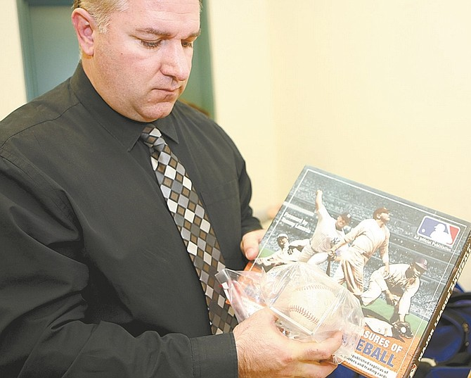 Photos by Shannon Litz / Nevada AppealCarson City Sheriff's Detective David LeGros shows a signed baseball and memorabilia that haven't been claimed, above, two rings, below, and a gold figurine, right, that were recovered from the burglaries.