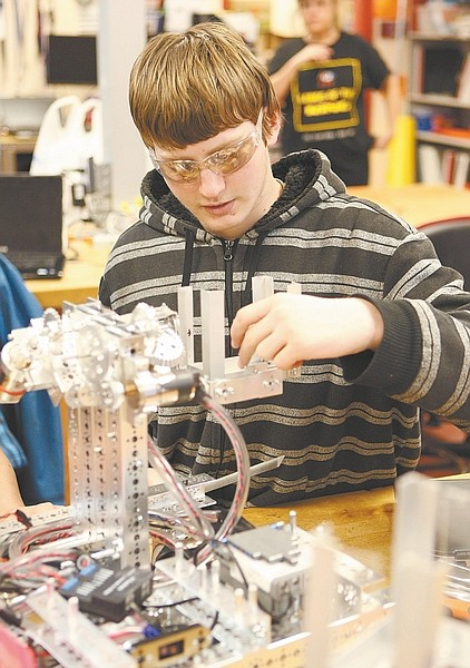 Photos by Shannon Litz/Nevada AppealLeft: Nate Shek, of the Silver State Charter High School team Robo Magic, works on the team's robot on Saturday.