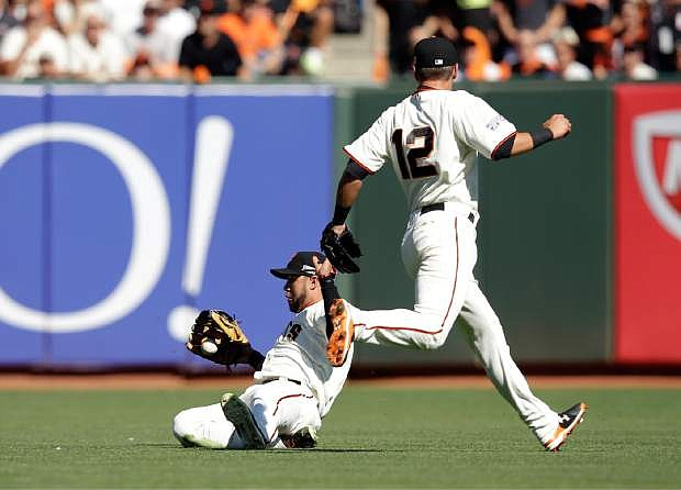 San Francisco Giants center fielder Gregor Blanco (7) drops a ball hit by Washington Nationals  Anthony Rendon in the first inning of Game 3 of baseball's NL Division Series in San Francisco, Monday, Oct. 6, 2014. On the right is San Francisco Giants second baseman Joe Panik (12).  (AP Photo/Ezra Shaw, pool)